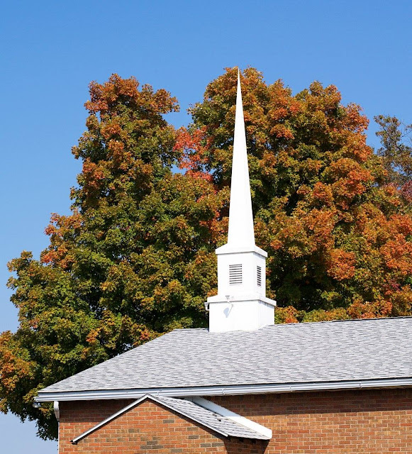 A white church steeple in front of a colorful fall tree.