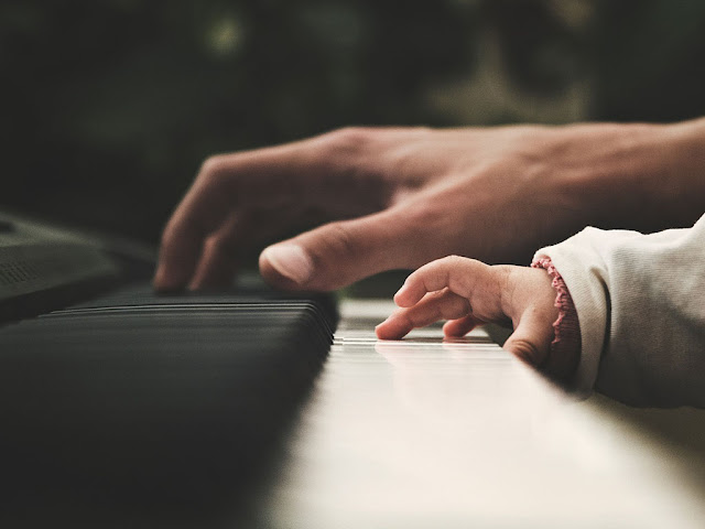 Adult and child's hands playing piano