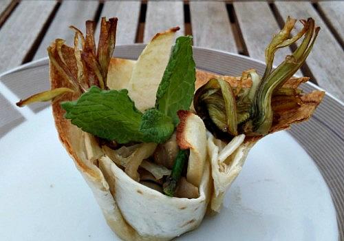 Unas tazas hechas con tortillas de trigo rellenas de manzanas y habas