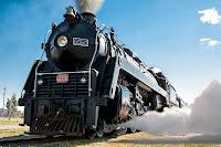 Üstünden duman çıkarak ve altından buhar püskürterek ilerleyen eski bir lokomotifin önden görünüşü