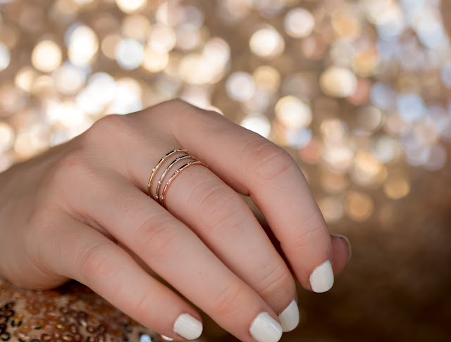 Diamond twinkle bands in three metal colors, yellow, white & rose gold stacked and worn together on hand.