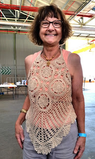 Rosalie is posing for the camera. She is wearing light grey pants with an apricot tank top which is covered by a natural coloured crocheted halter-neck top.  The bodice section comprises circular motifs (4 large in a diamond arrangement) and shell stitches radiating down towards the hem. The hem finishes in a central point with ruffled shell patterns along it.