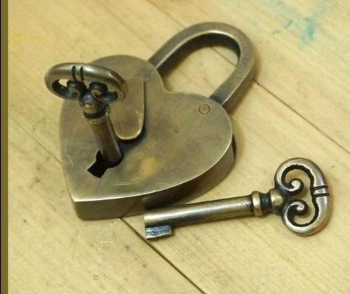 Um cadeado de bronze em forma de coração e dua chaves.