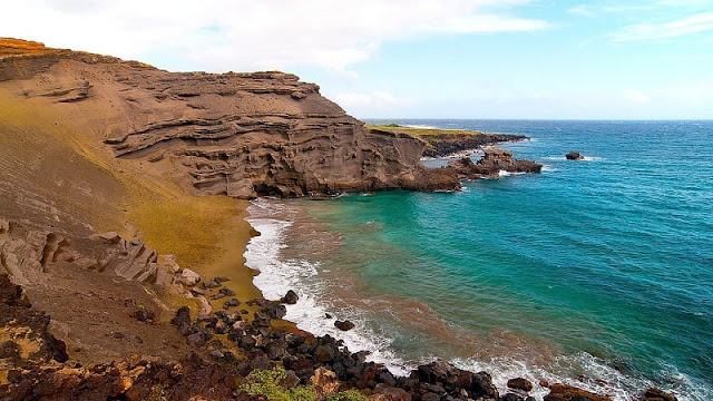 pemandangan tebing yang dipenuhi pasir hijau di Papakolea Beach