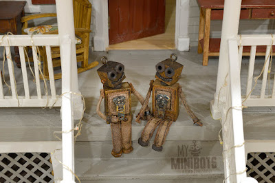 My tiny robots sitting on a doll house porch - Robin Davis Studio