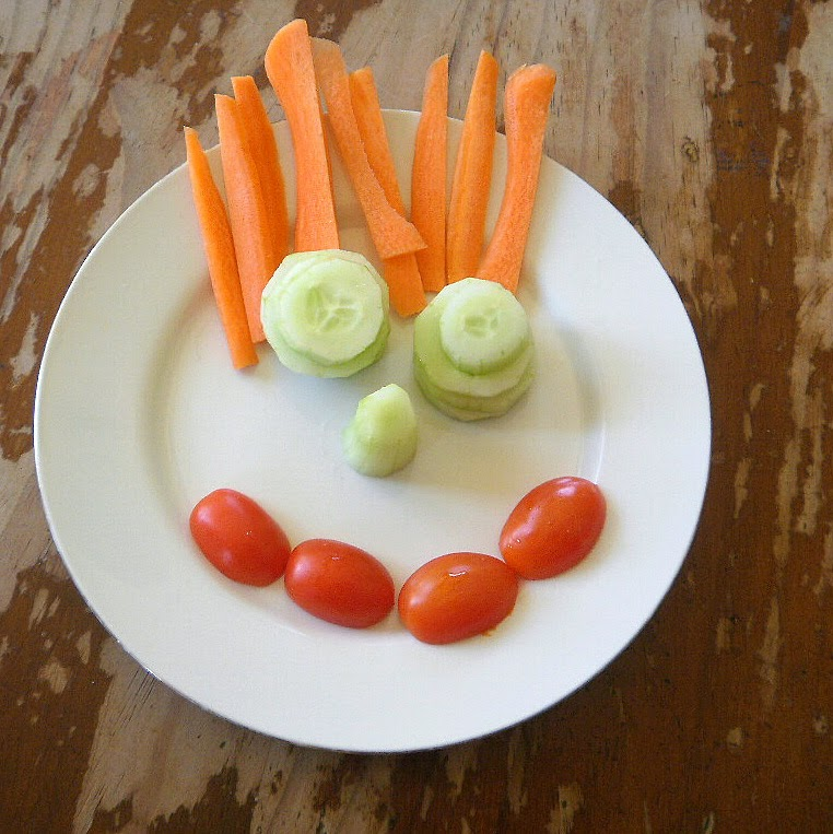 fresh vegetables on a plate arranged to look like a face