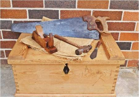 Different tools lying on a carpenter's toolbox, a brick wall in the background