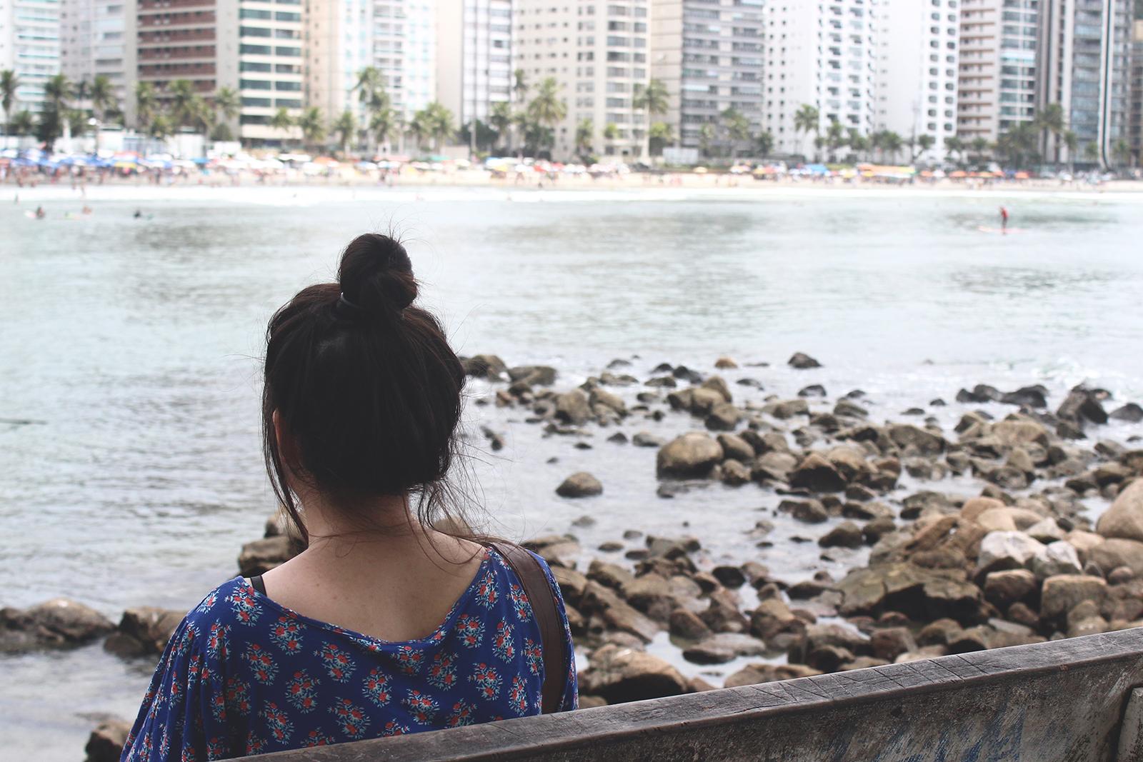 garota sentada vendo mar