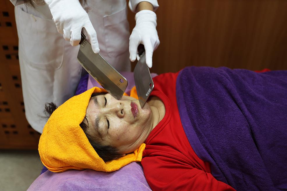 """Масажист проводить """"масаж ножем"""" на жінці в Тайбеї, Тайвань."""