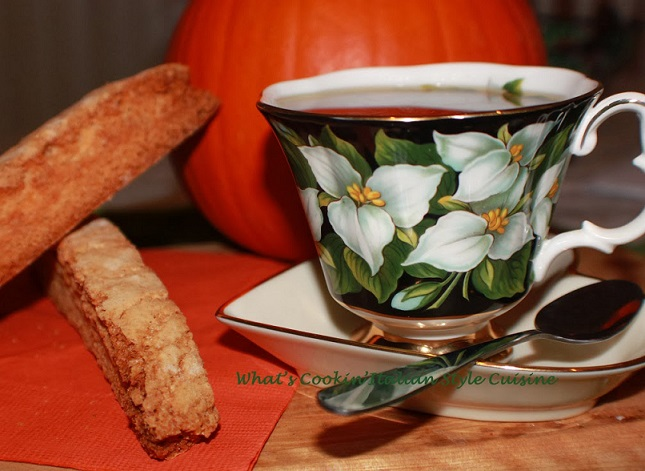 this is how to make a pistachio pumpkin biscotti Italian Cookies with a cup of espresso that has leaf green design on it and a demitasse spoon there is a real pumpkin in the background also