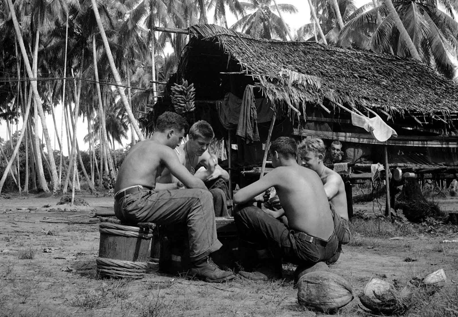 U.S. soldiers from every state shipped off to war. Here, after taking part in the fighting, soldiers (two from Detroit) relax by playing cards in a palm grove behind the lines at Buna, New Guinea on January 13, 1943. The players are, left to right: Pfc. Sam Demopolis, Detroit, Michigan,; Pfc. Robert Trudell (facing camera) of Detroit; Corp. James Williams (back to the camera); Genesee Depot, Wisconsin; and Pvt. Laurence Thompson, Duluth, Minnesota.