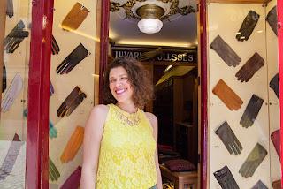 pessoa com blusa amarela sorrindo na porta da luvaria em vitrine cheia de luvas coloridas