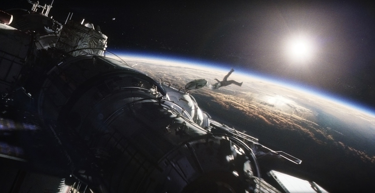 The small figure of an astronaut floating alongside the space station with the curved horizon of Earth in the distance and the sun beyond it