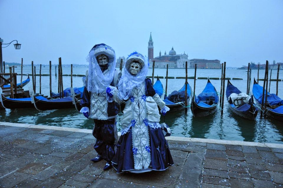 Masks pose with gondolas and the island of San Giorgio Maggiore as a backdrop