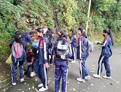 Girls clean up a hillside in Darjeeling
