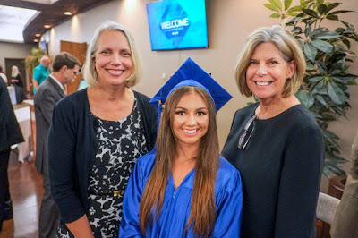 Image of student in cap and gown with family members