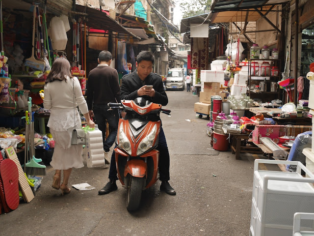 man using his mobile phone while sitting on motor scooter at Yanjiatang Lane (晏家塘巷) in Changsha