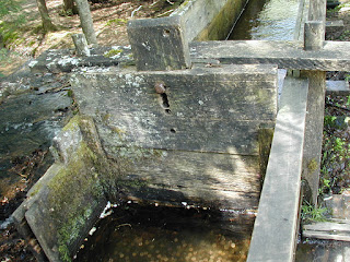 A wood gate in the flume controls the amount of water that goes to the water wheel.