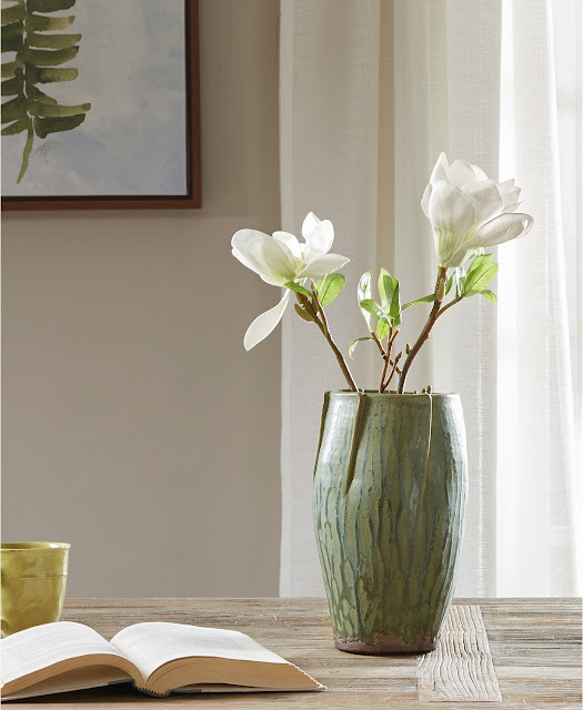 green pottery vase with magnolia branches