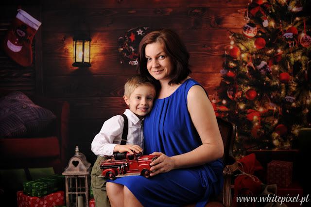 mały chłopiec z mamą na fotografii w scenerii świątecznej z choinką w góralskim domku
