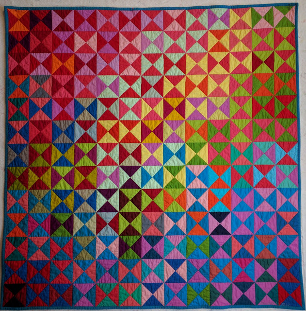 The quilt glows with color like stained glass and the QSTs in a range of colors sweep across the surface- red, blue, green, yellow, purple, lavender, pink, orange, and megenta.