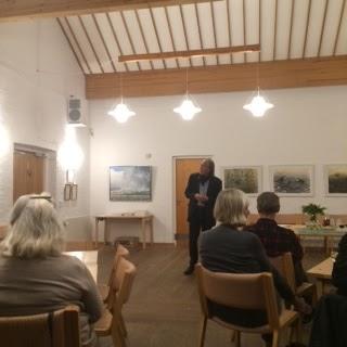 Jens Gregersen i salen blandt tilhørere og billeder