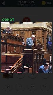В сенате за трибуной выступает мужчина, его слушают остальные сенаторы