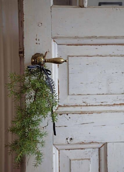 Christmas greenery on vintage brass door lever #FrenchChristmas #vintagedoor