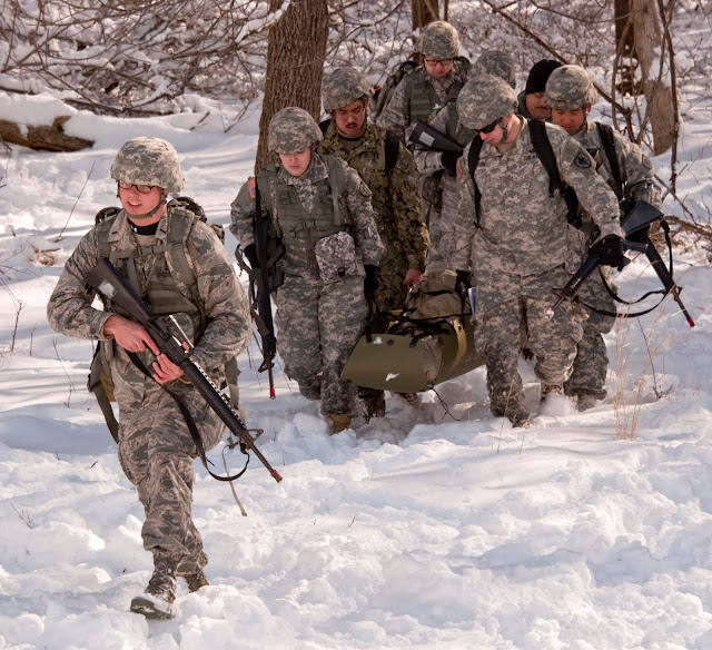military students carry a loaded gurny through snow