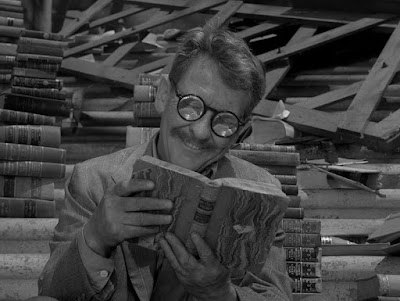 Burgess Meredith in a Twilight Zone episode, sitting on stairs reading a book.