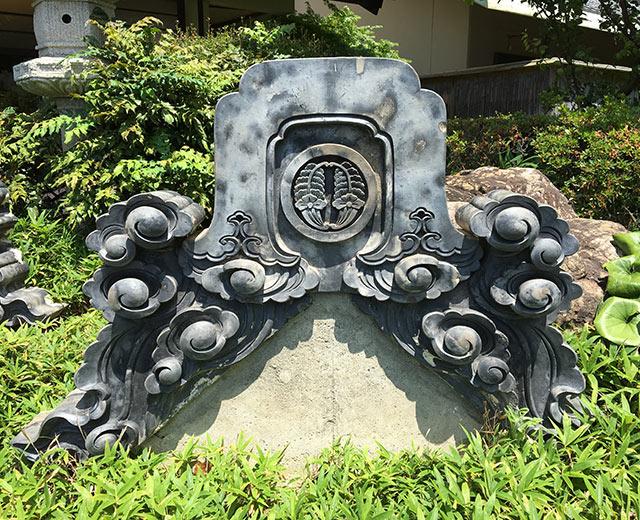 ホテル九重前に残されている丸に花抱き茗荷紋のあしらわれた堀江藩邸鬼瓦