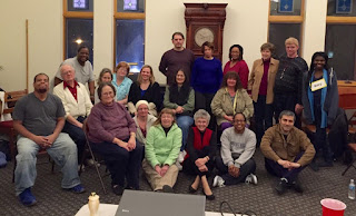 picture of a large group of people in a room, some are sitting on the floor, some on chairs, and some standing, they are members of the Deaf Bible study at Grace UMC.