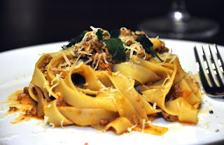Makaron tagliatelle z sosem bolognese posypane parmezanem i ozdobione natką pietruszki