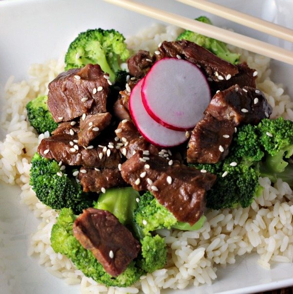 Slow Cooker Beef and Broccoli on a white plate with chop sticks