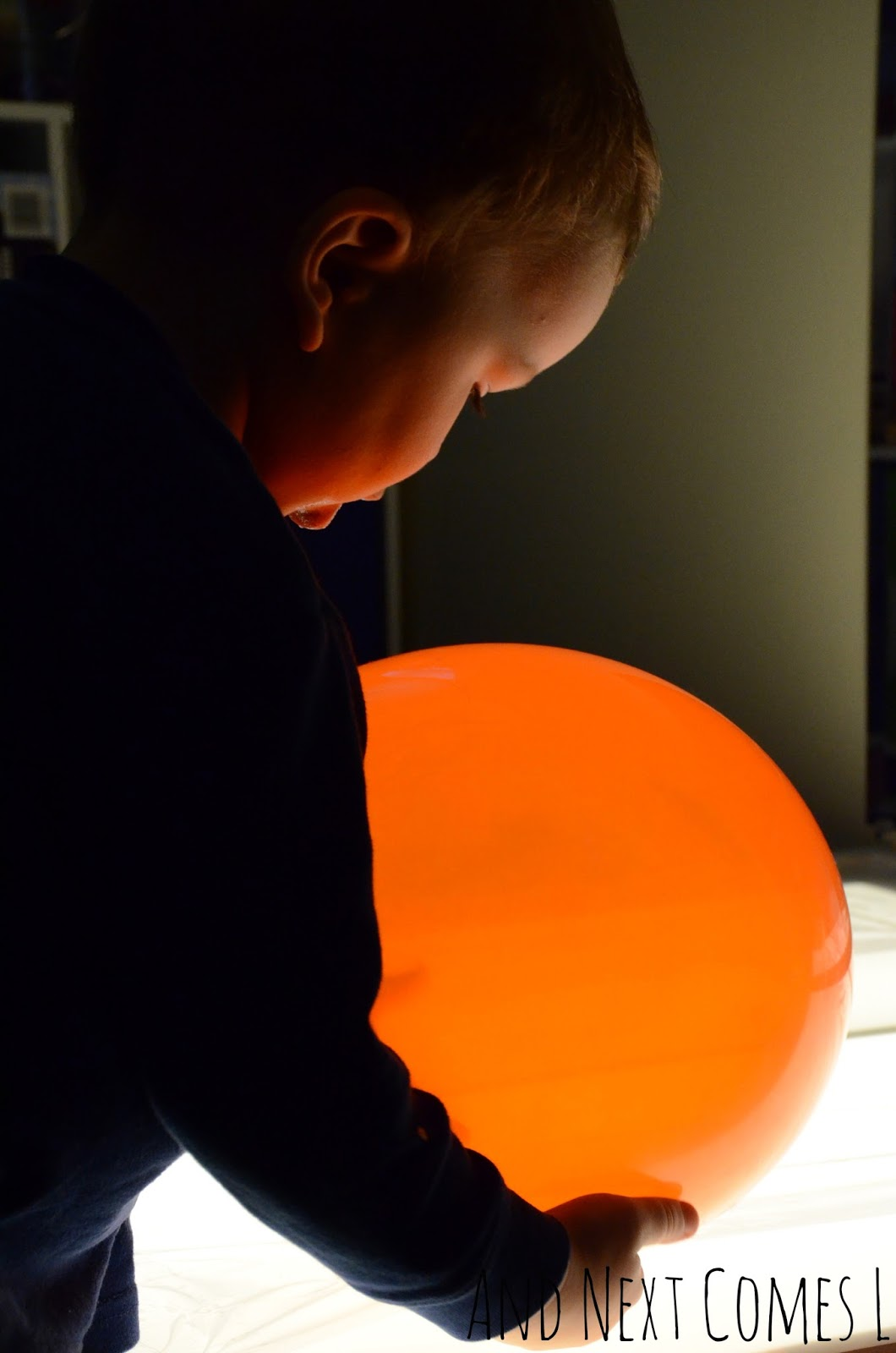 K checking out the balloons on the light table from And Next Comes L