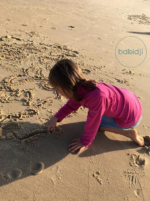 fille qui fait des coeurs dans le sable
