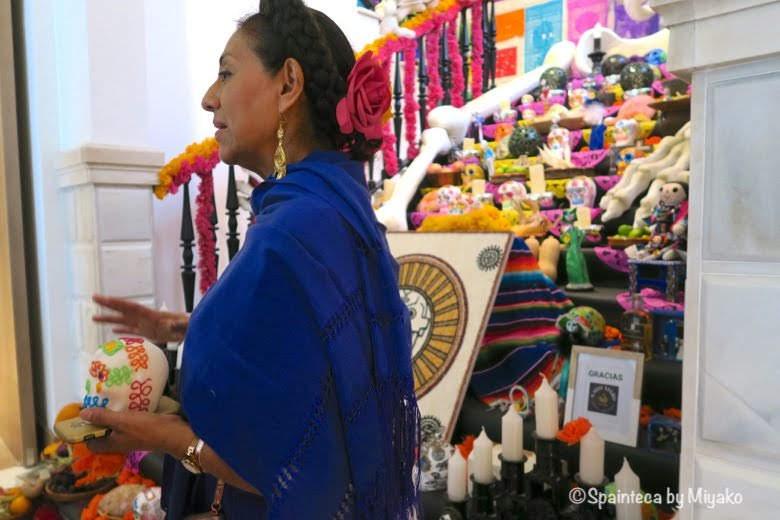 メキシコの家の祭壇の前で死者の日を説明する係の女性