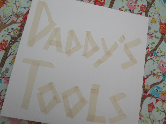 A canvas with masking tape lettering