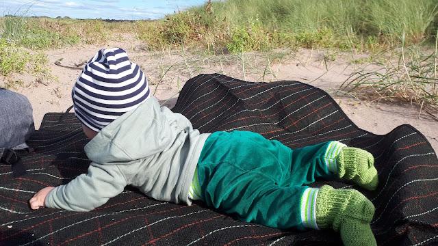Vihreät villasukat, raidallinen pipo, vauva rannalla