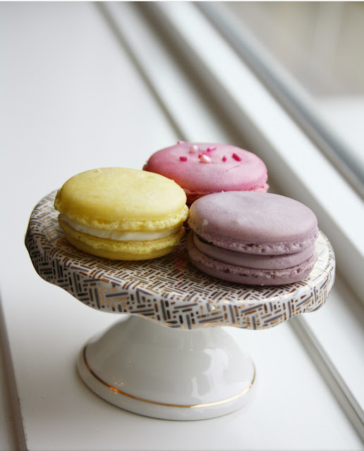 Raspberry, Blueberry and Lemon Macarons on a mini cake stand by a windowsill
