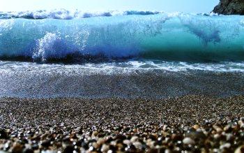 Wallpaper: Ocean wave over the shells beach