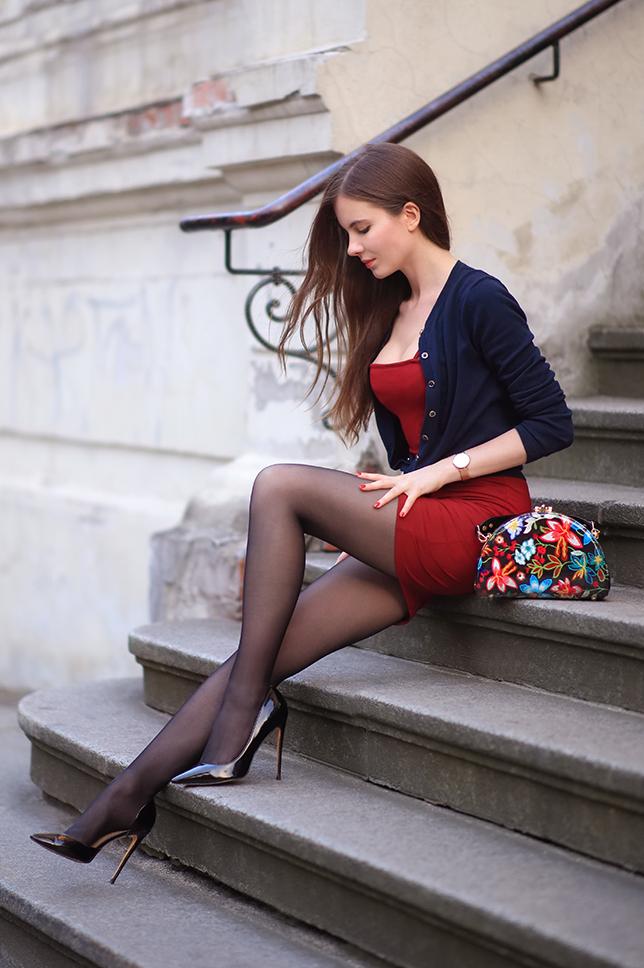 Bordowa obcisła sukienka, granatowy cardigan, czarne rajstopy i szpilki