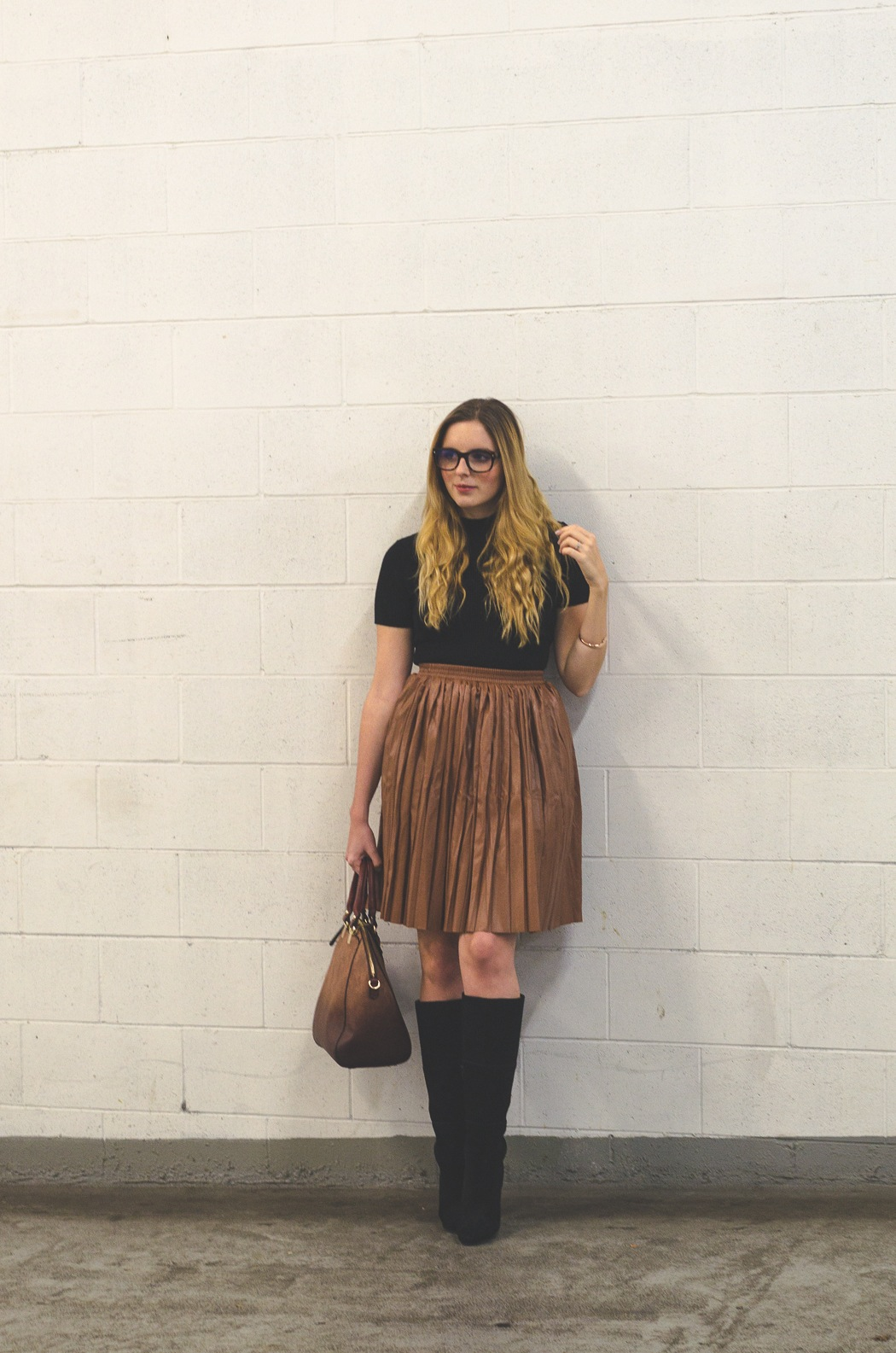 black turtleneck paired with leather camel tone midi skirt and black suede boots
