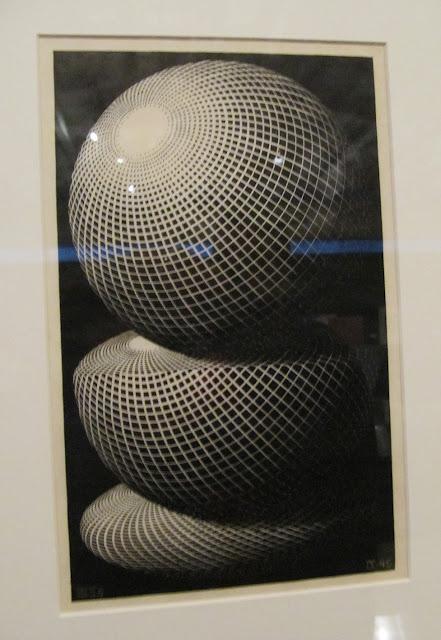 Obra de Echer composta por três esferas e com linhas gerando a sensação de movimento. Toda a peça é preto e branco.