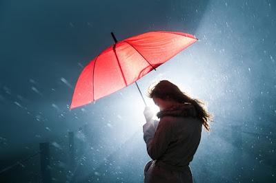 Chica en invierno por la calle con paraguas y luz de fondo