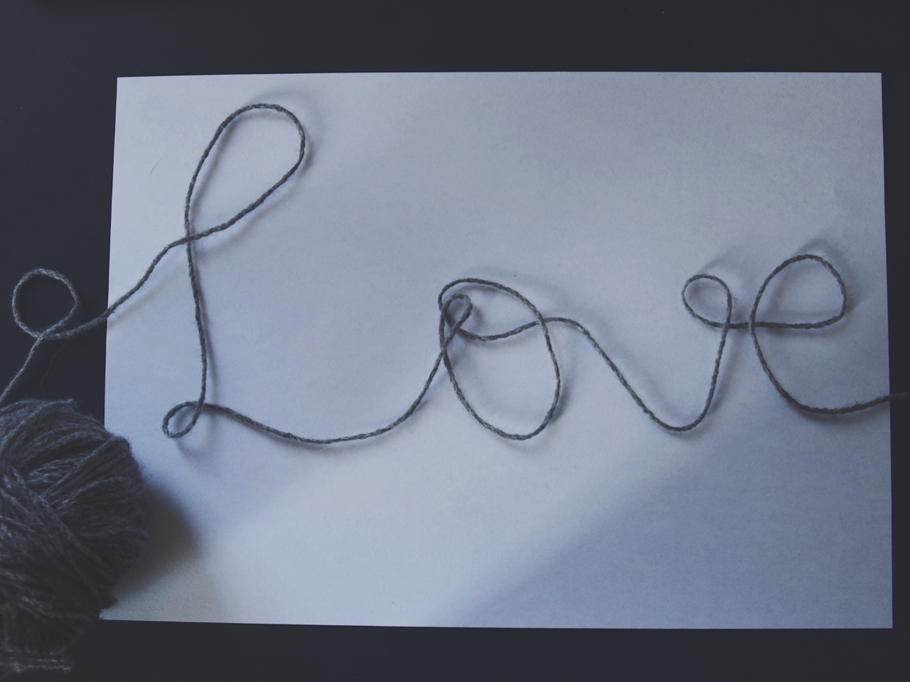 On a white sheet of paper the word »Love« laid out of grey wool