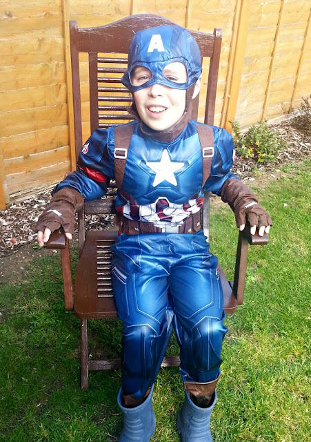 Boy wearing Captain America Costume Seated