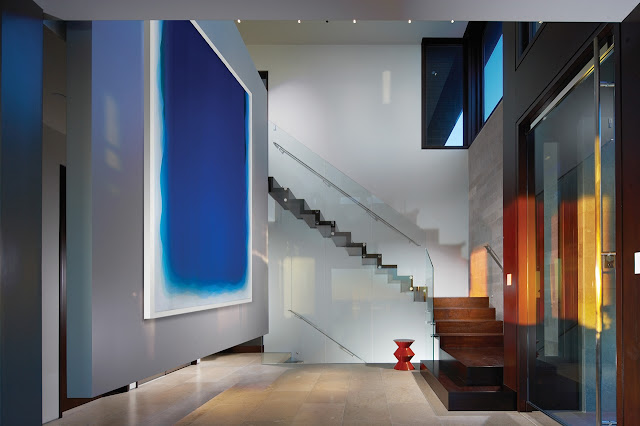 Picture of large high ceiling hallway with modern staircase and abstract painting on the wall