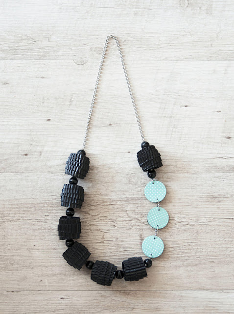 crimped black paper bead necklace with dotted aqua and white discs