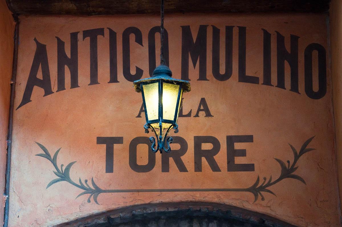 Shop fascia with a lit lantern, Borghetto, Veneto, Italy